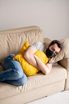 헝겊 마스크에 긴장된 젊은 남자가 소파에 베개를 껴안고 한 지점에서 잠긴 눈으로 보는 검역에서 스트레스를 받았다.