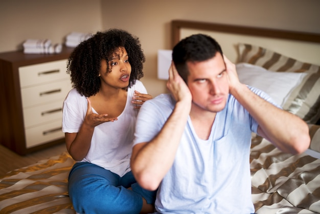 Nervous young man trying to doesn't listen to his girlfriend in the bedroom.
