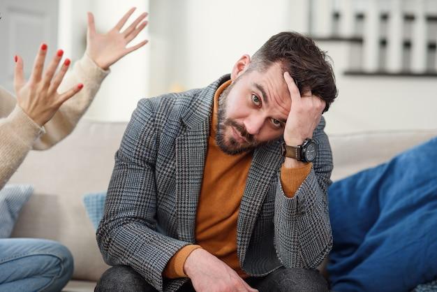 Нервный молодой человек пытается не слушать свою девушку в спальне.