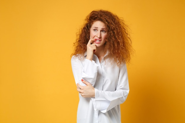 노란색 오렌지 벽에 고립 된 캐주얼 흰색 셔츠 포즈에 긴장 젊은 빨간 머리 여자 소녀