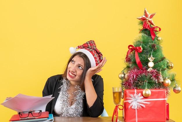 Donna d'affari nervosa in vestito con cappello di babbo natale e decorazioni di capodanno che tiene documenti e si siede a un tavolo con un albero di natale su di esso in ufficio
