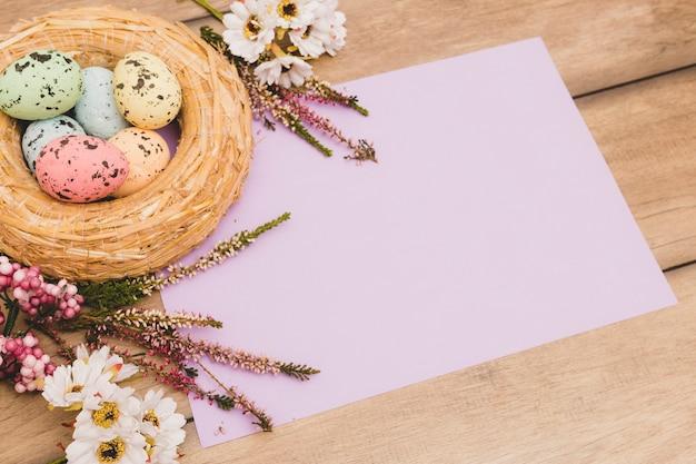 Гнездо и цветы возле бумаги