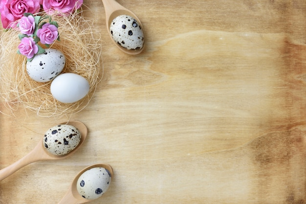 Nest eggs and flowers on wood background.