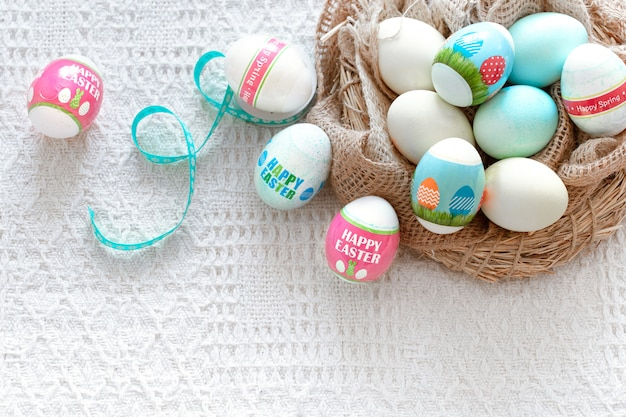 A nest of hay with beautiful easter colored eggs on light.