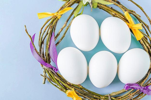 小枝と白い卵とカラフルなリボンの巣