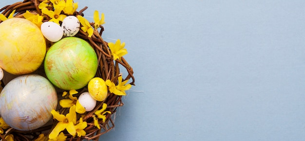 파란색 배경에 꽃 색된 계란과 둥지. 부활절 텍스트를위한 공간을 복사하십시오. 배너