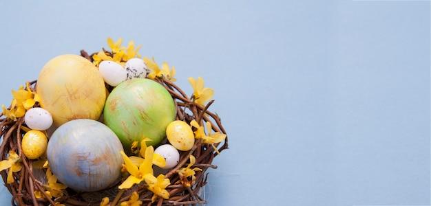青色の背景に花と着色された卵の巣。イースターのテキストのためのスペースをコピーします。バナー