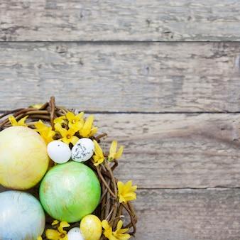 木製のテクスチャの上に花と着色された卵の巣。イースターテキストのコピースペース