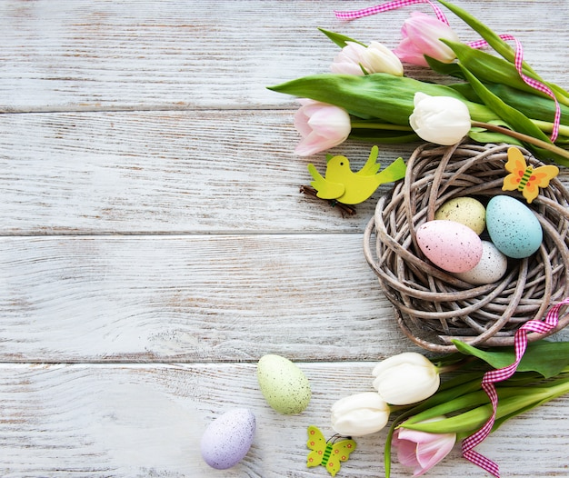 Nest with  easter eggs and tulips bouquet