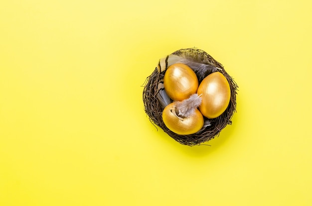 金の背景の上の巣に金の装飾的な卵と羽と巣