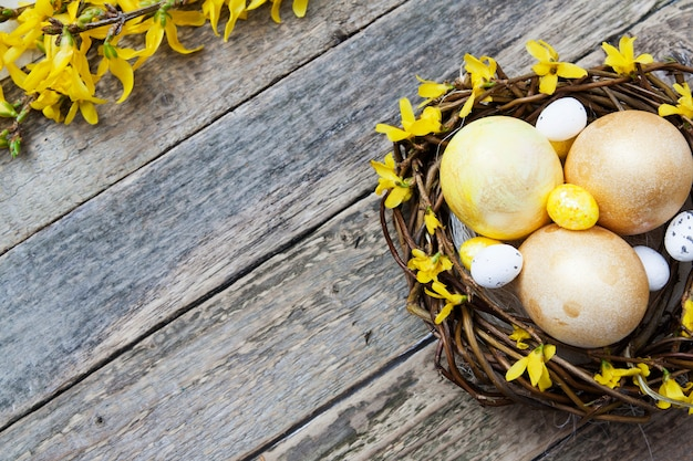 木製のテクスチャの上に花と黄金と黄色の卵の巣。イースターテキストのコピースペース