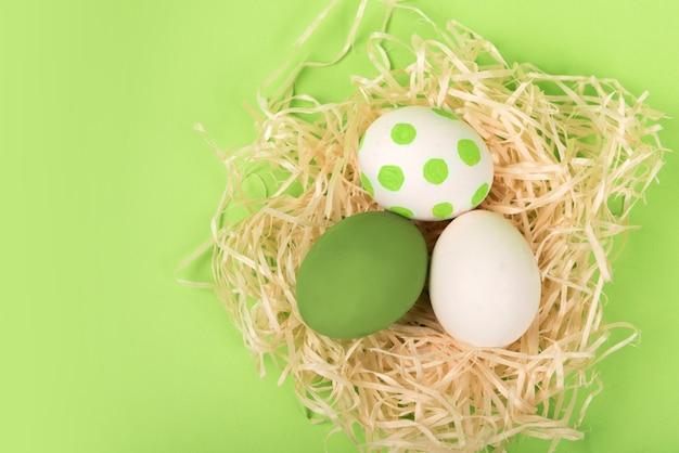 Гнездо с зелеными и белыми пасхальными яйцами на зеленом фоне