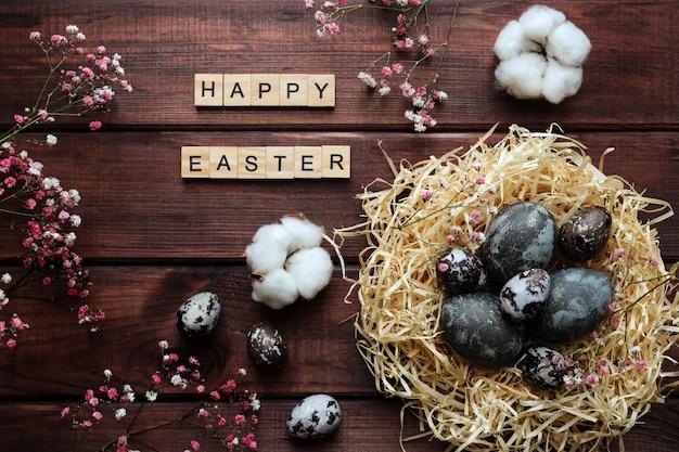 自然に染められた卵の巣綿の花の装飾と碑文暗い木製のテーブルに木製の文字から作られたハッピーイースター