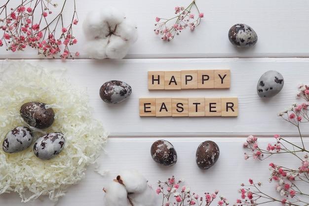 自然に染められた卵の巣綿の花の装飾と碑文ワイト木製テーブルの木製の文字から作られたハッピーイースター