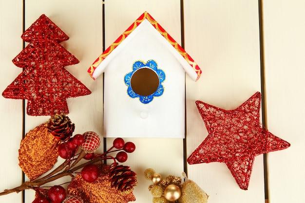 Скворечник и рождественские украшения на деревянных фоне