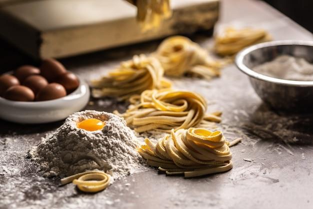 キッチンプレップテーブルのキッチンプレップテーブルに卵、卵黄、小麦粉を入れた新鮮なフェットチーネパスタの巣。