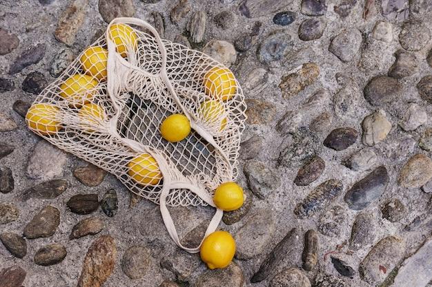 石畳の道に横たわっている新鮮なレモンの山とネットバッグ