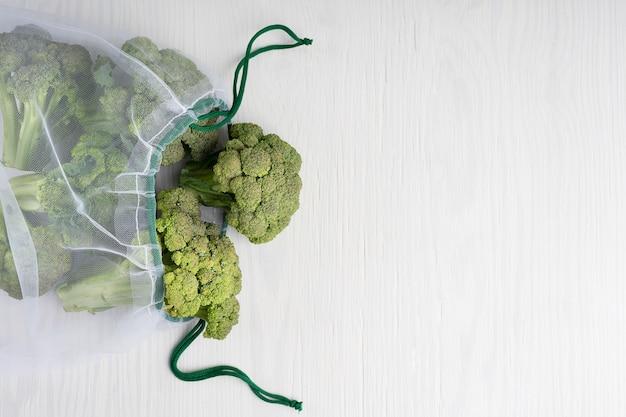 白い木製の緑の生のブロッコリーとネット持続可能なバッグ