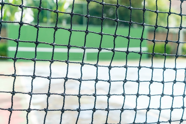 Net with empty tennis court background