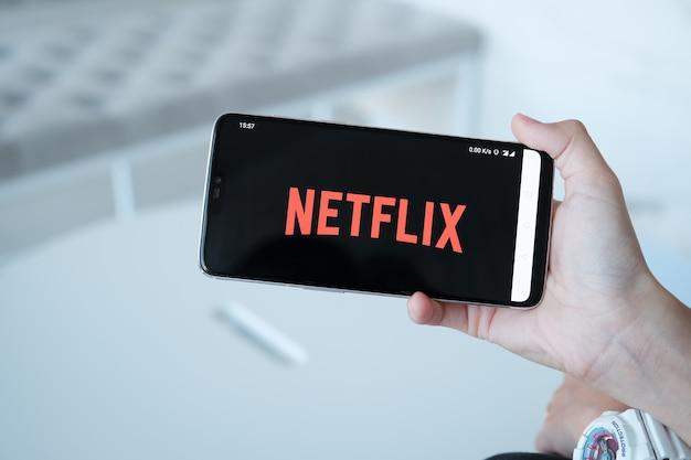 テレビ画面上のnetflixロゴ。ノートパソコン画面上のnetflixアプリ。 netflixは、テレビのエピソードや映画を視聴するための国際的な主要なサブスクリプションサービスです。