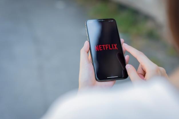 女性がスマートフォンの画面でnetflixアプリを使用する