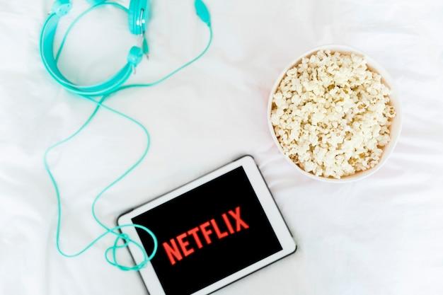 Netflixロゴ付きのタブレットに近いポップコーンとヘッドホン