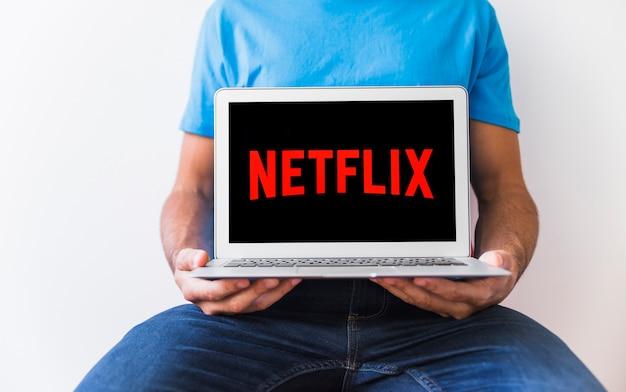 Человек с капюшоном, держащий ноутбук с логотипом netflix