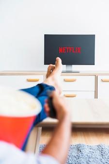 Netflixショーを見ているポップコーンとリモコンを持って