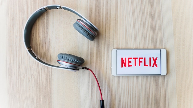 Netflixロゴ付きスマートフォンに近いヘッドフォン