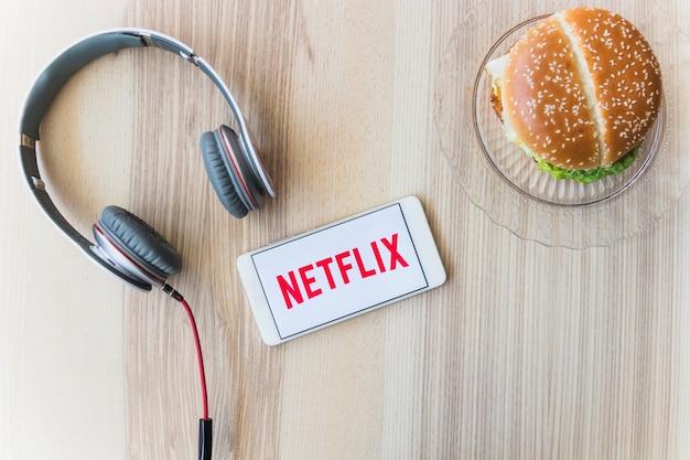 Netflixロゴ近くのヘッドフォンとハンバーガー