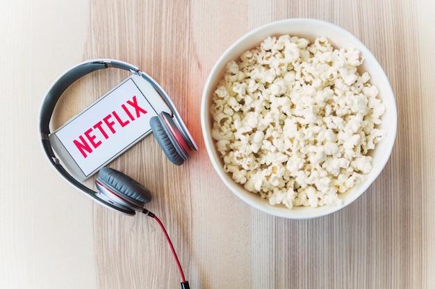 Netflixロゴ付きのスマートフォンに近いヘッドフォンとポップコーン