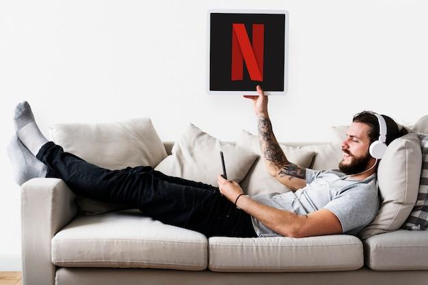 Netflixのアイコンを見せている男