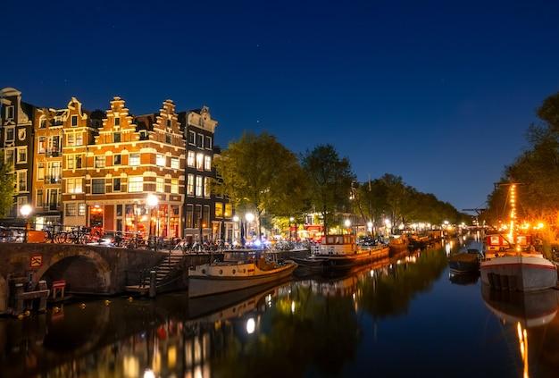 オランダ。アムステルダムの夜の運河で落ち着いてください。住宅のはしけやボートが係留されています。伝統的な家屋や橋の水面での反射