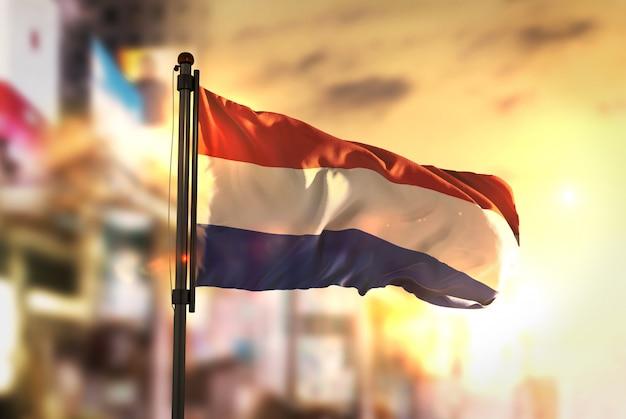 Netherlands flag against city blurred background at sunrise backlight