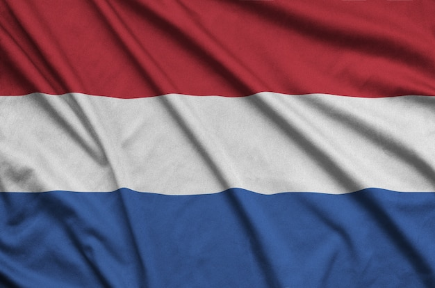 Netherlands flag is depicted on a sports cloth fabric with many folds.