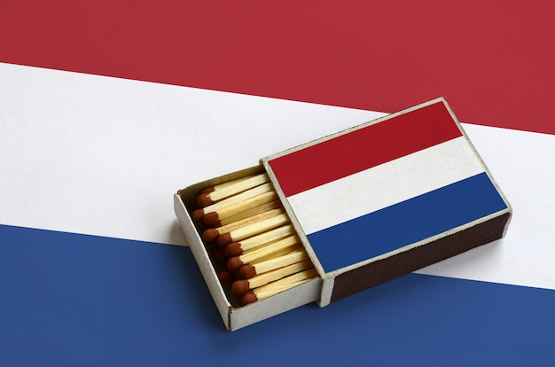 Netherlands flag  is shown in an open matchbox, which is filled with matches and lies on a large flag