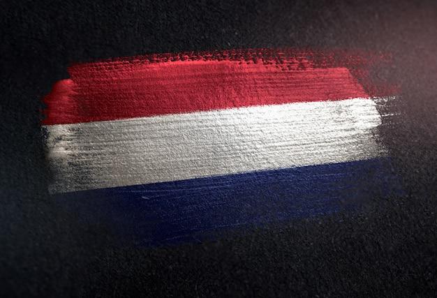 Netherlands flag made of metallic brush paint on grunge dark wall