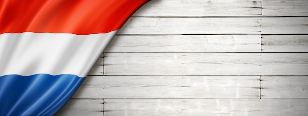 Netherlands flag on old white wall. horizontal panoramic banner.