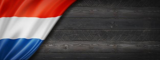 黒い木の壁にオランダの旗。水平方向のパノラマバナー。