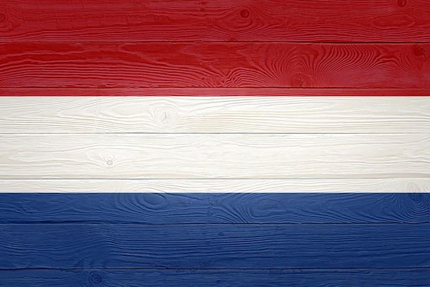 古い木の板の背景に描かれたオランダの国旗