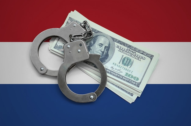 Netherlands flag  with handcuffs and a bundle of dollars. currency corruption in the country. financial crimes