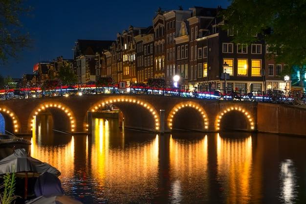 네덜란드. 암스테르담에서 밤에 조명된 운하입니다. 많은 자전거가 울타리 옆에 주차되어 있습니다. 빛나는 창문이 있는 전통 가옥