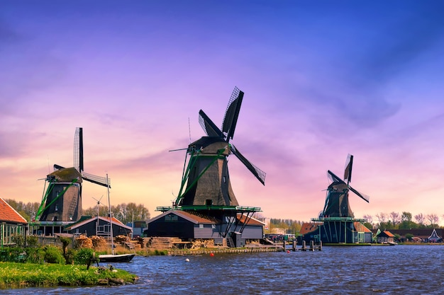 Нидерланды сельский пейзаж. традиционные голландские ветряные мельницы с каналом в деревне заансе сханс во время заката.