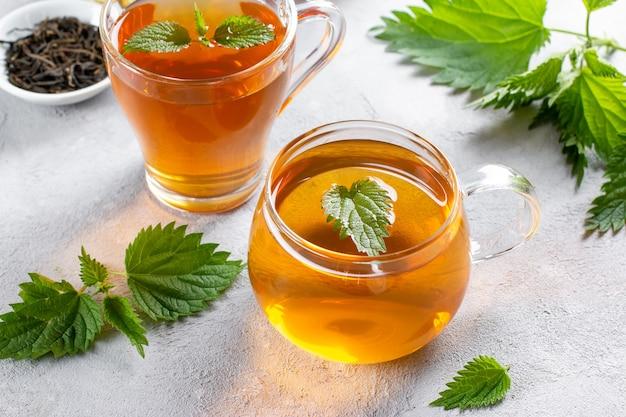 Чай из крапивы в стакане со свежей крапивой внутри, на столе