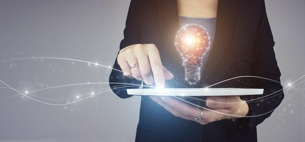 전구와 네트워크 밝은 아이디어. 회색 배경에 디지털 홀로그램 전구 기호가 있는 사업가 손에 있는 흰색 태블릿. 혁신, 브레인스토밍, 영감 및 솔루션 개념.