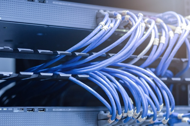 Network cables connected in network switches - data center concept.