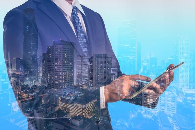 스마트 시티 배경에 홀로그램이 있는 전화를 들고 있는 네트워크 개념 비즈니스 맨