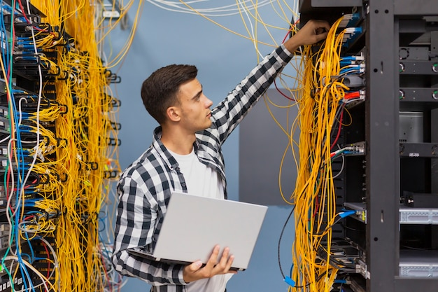 Network engineer on server room with a laptop medium shot