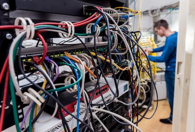 Сетевой инженер работает в серверной комнате. подключение сетевых кабелей к коммутаторам
