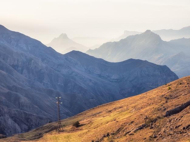 秋の霧の山の丘のワイヤーと電柱のネットワーク。ダゲスタンの大気中の山の霧の風景。